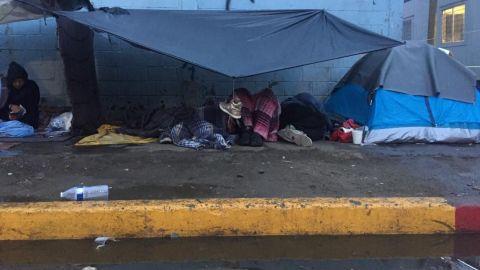 Migrantes en Tijuana, amanecen mojados y con frío