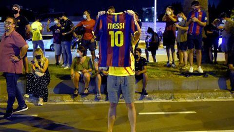Cientos de aficionados del Barcelona reciben a su equipo en el Camp Nou