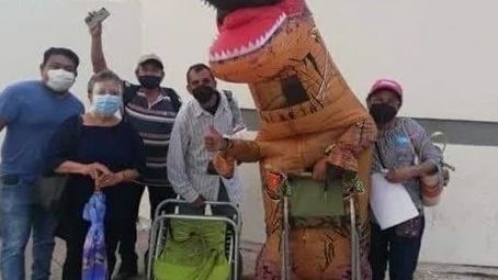 Joven se viste de dinosaurio para acompañar a su mamá a vacunarse